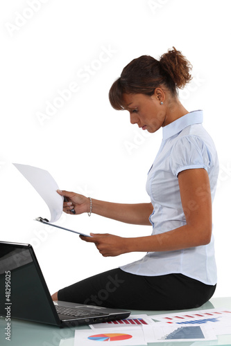 Woman perusing documents at her desk