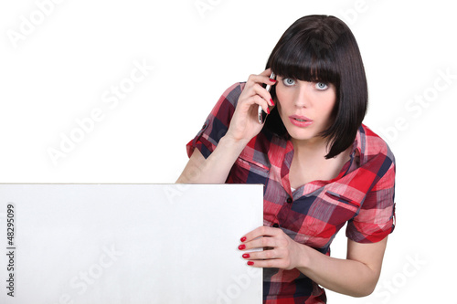 Brunette making telephone call by blank panel