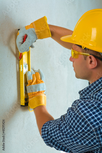 a worker layering on cocrette wall