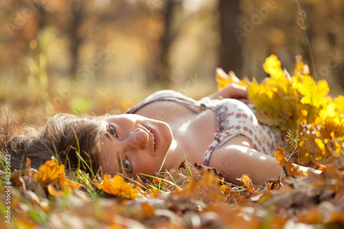 Young woman lies in  autumn park