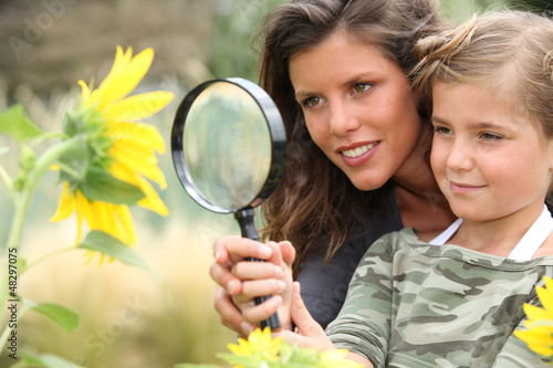 Young mum and daughter looking at a sunflower
