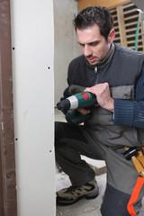 Man drilling an interior wall