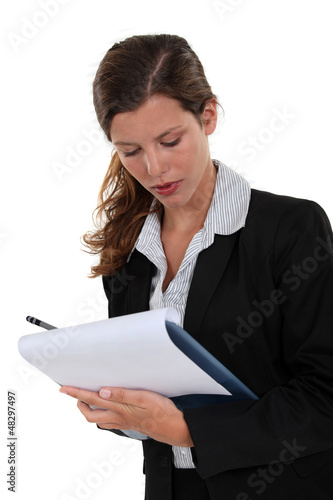 Brunette writing on clip-board