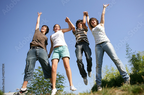 Happy teenagers jumping in air