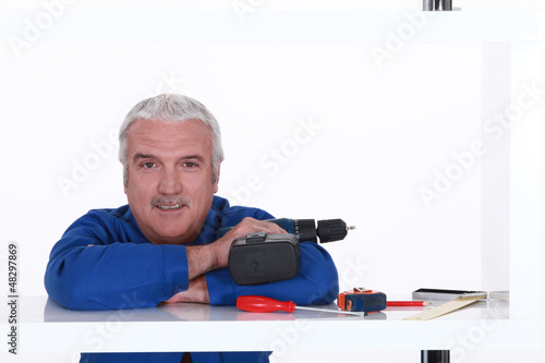 Man with his tools leaning on a shelf