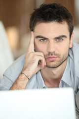 Relaxed man using laptop