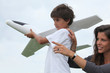 Mother and son playing with a large model toy aeroplane