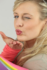 Blonde woman with files blowing a kiss