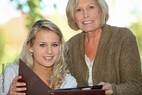 Senior and her granddaughter looking at photos