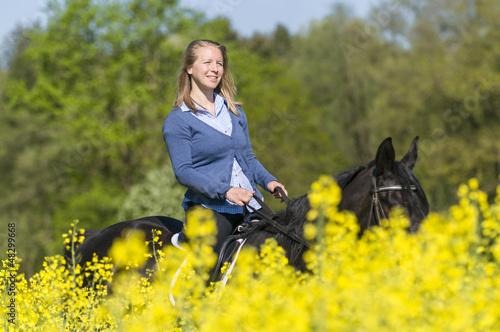 Reiterin zwischen blühenden Feldern
