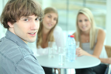 Teenager sitting with his female friends