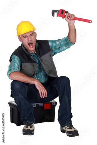 Cheerful builder sat on tool box
