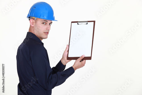 Man in a hardhat with a blank clipboard