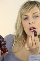 Young fair-haired woman eating grapes