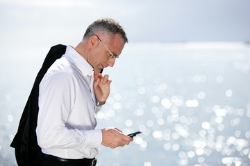 Businessman sending a text message by the seaside