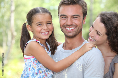 Young family stood in garden