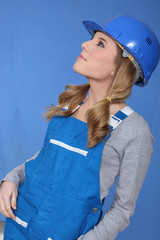 Woman in blue overalls and hardhat