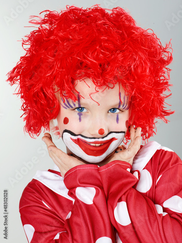 Beautiful child as a funny clown with red hair