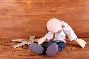 Wooden puppet sitting on wooden background