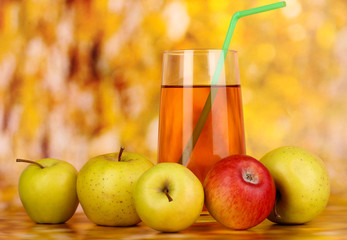 Useful apple juice with apples around on autumn background