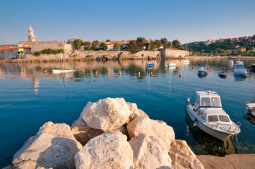 Stones and boat on little port beside old town Krk - Croatia
