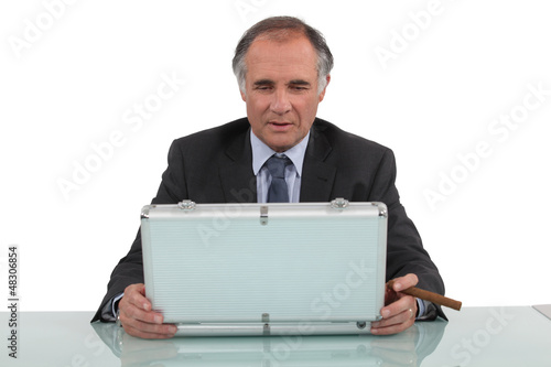 A businessman looking in a briefcase and smoking a cigar.