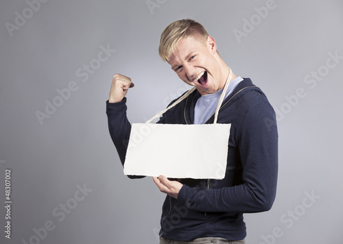 Overjoyed man presenting empty signboard.