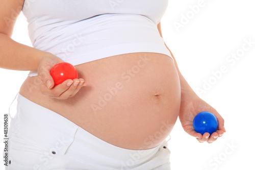 Schwangere Frau hält blauen und roten Ball