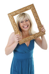 Hübsche Frau schaut lächelnd durch goldenen Bilderrahmen