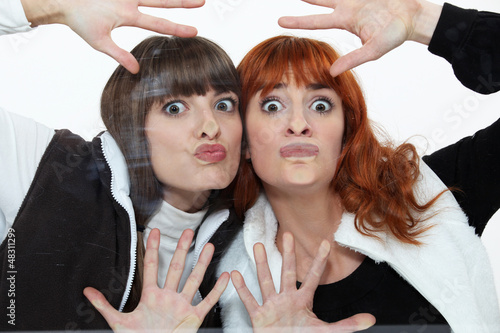 Two women pressing their faces against glass