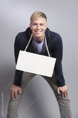 Joyful likable man showing empty signboard.