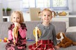 Happy little girls eating banana at home