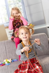 Little girls playing with mother's necklaces