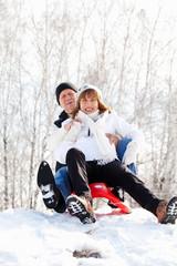 Mature couple sledding
