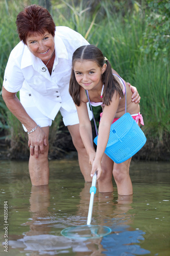 Little girl fishing in pond with mother