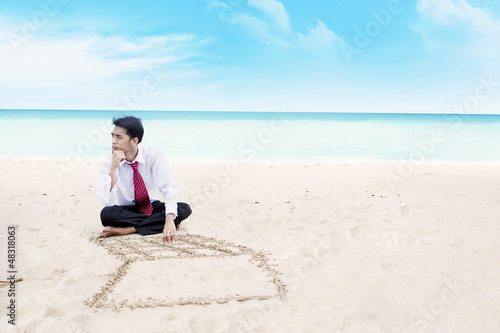 Businessman thinking on a beach