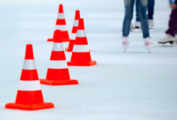 Ice skaters legs and red white striped cones on the ice rink