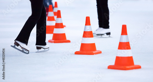 Red white striped cones on the ice rink