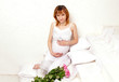 The smiling pregnant young woman in a white dress with union of
