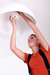 Woman fixing ceiling light