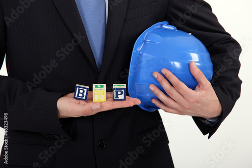 Businessman holding a hard hat and letter blocks