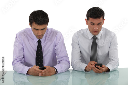 Businessmen sending text messages simultaneously