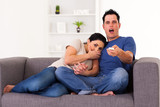 young couple watching scary horror movie at home