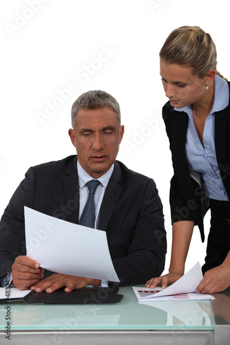 Boss showing paperwork to assistant