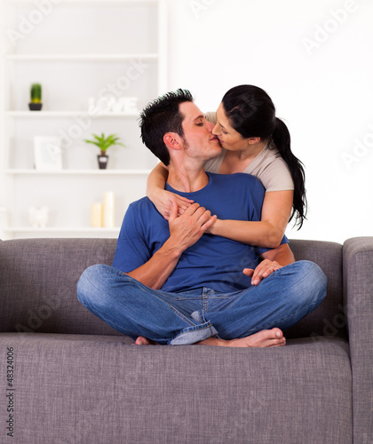 young couple kissing on sofa at home