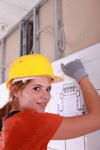 A female electrician installing a wire board.