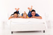 beautiful young family lying on bed