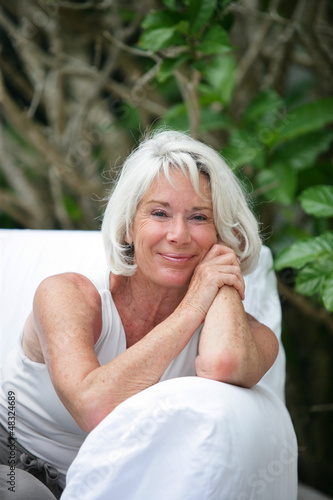 Senior woman sitting on an outdoor sofa
