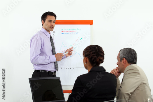 Man stood by flip-chart giving presentation to colleagues