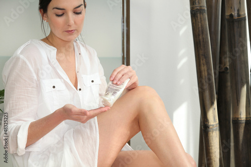 Woman smoothing cream onto legs